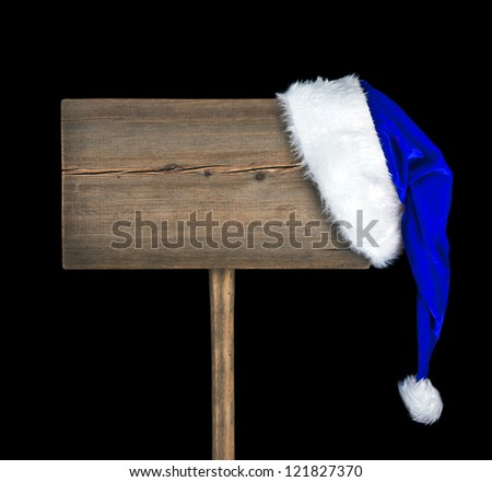 Wooden road sign with blue Santa hat isolated on a black background. Christmas signboard