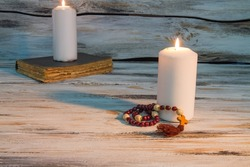Wooden rosary and burning candle in a church.