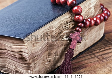 wooden rosary lying on a closed Bible