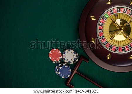 Wooden Roulette Drum on Green Casino Felt Table, Border BAckground, Top View.