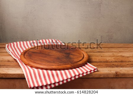 Wooden round board on tablecloth over rustic background