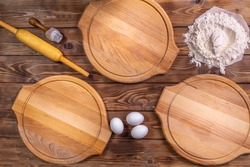 Wooden round pizza boards, chicken eggs, a mound of wheat flour and a rolling pin on a brown board background. Flat layout.