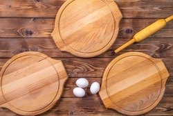 Wooden round pizza boards, chicken eggs and rolling pin on a brown board background. Flat layout.