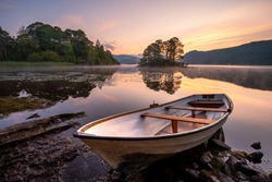 Wooden rowing boat on lake shoreline with beautiful view of calm misty Derwentwater in the Lake District, UK. Travel background of British Summer landscape.