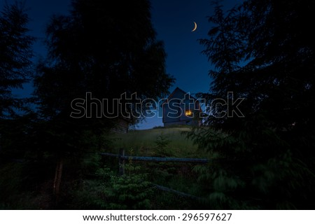Wooden rural house on the green hill between of big carpathian spruce trees at twilight hour. New moon over it.