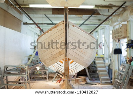 Wooden sailboat being planked in nice shop