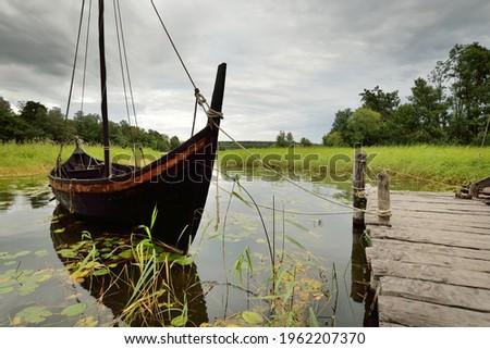 Wooden sailing boats moored to a pier. Birka, Björkö island, lake Mälaren, Sweden. Atmospheric landscape. Travel destinations, landmarks, sightseeing, history, historical reenactment, viking age Stock fotó ©
