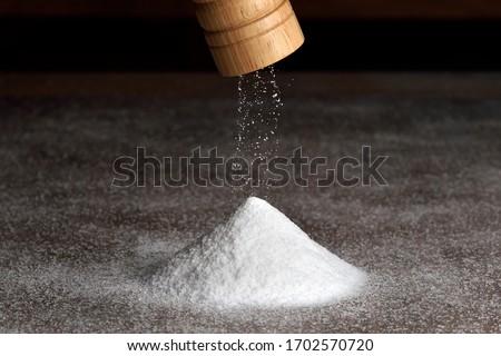 Wooden salt grinder and pile of salt. Salt falls from the grinder on a table full of salt.  Foto d'archivio ©