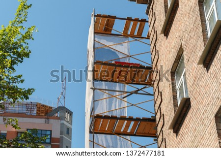 wooden scaffolding on building facade, construction site with framework on buiding