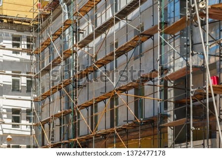 wooden scaffolding with ladders on gray building facade, construction site with framework on buiding