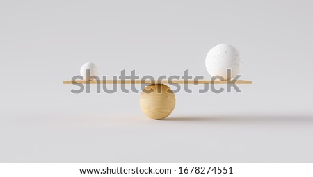 Photo of  wooden scale balancing one big ball and one small ball. Concept of harmony and balance