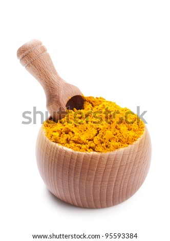 Wooden scoop in bowl full of dry turmeric isolated on white background