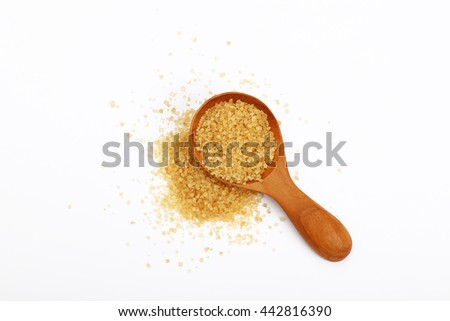 Wooden scoop spoon of brown cane sugar with pinch of sugar spilled around isolated on white background, top view #442816390