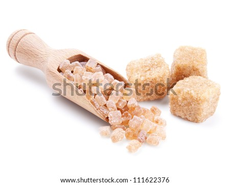 wooden scoop with cane sugar crystals isolated on white