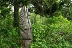 Wooden sculpture of a bird in a clearing in a forest Park.