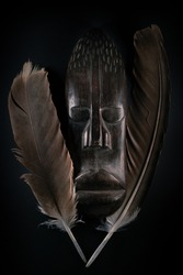 Wooden sculpture of human face in African style with big feathers around it. Dark wood carving. African tribal mask isolated on black background. Art and culture of African people. Black history.