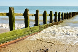 Wooden sea breaker with lapping waves on the sand and deep blue sea in summer