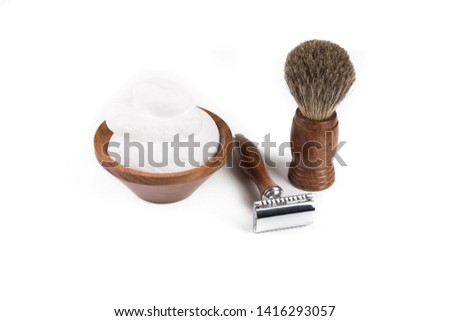 Wooden shaving razor and shaving brush with shaving foam on a white background
