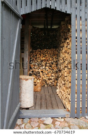 Wooden shed filled with piles of chopped firewood #670734619