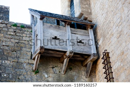 wooden shed-like structure of a hoarding on the stone wall of castle Beynac as part of the castle defense.