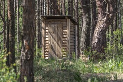 Wooden shed. Street toilet. A piece of civilization. Restroom in the woods. Amenities in the wild. Shed in a woods. Rest in the country.
