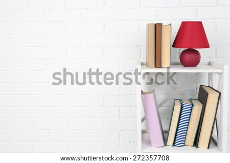 Wooden shelf with books and lamp on brick wall background