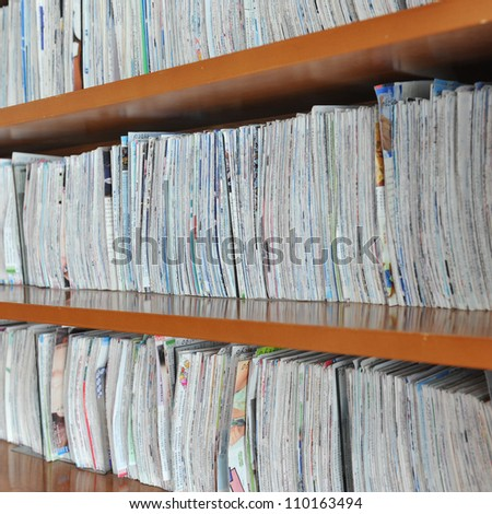 wooden shelf with brochures and piles of paper