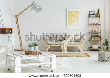 Shutterstock Wooden shelf with plants, balls and candles next to designed sofa with patterned pillows