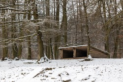 Wooden shelter built in the winter snowy forest for animals.