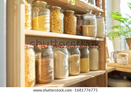 Wooden shelves in pantry for food storage, grain products in storage jars.