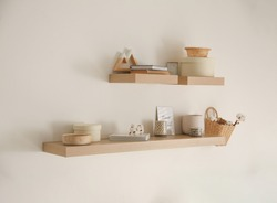 Wooden shelves with books and different decorative elements on light wall