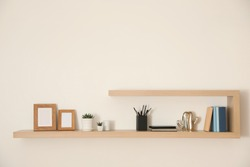 Wooden shelves with books, photo frames and decorative elements on light wall