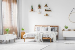 Wooden shelves with plants above a comfortable double bed in a spacious apartment interior with white furniture and walls