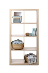 Wooden shelving unit with baskets and different stuff isolated on white