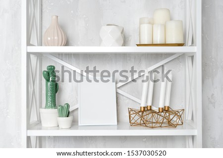 Wooden shelving unit with decor near grey wall. Bookcase with photo frame mockup and candles, living room interior details