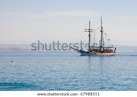 Wooden ship sailing across the Red Sea with the people on board, Eilat, Israel.