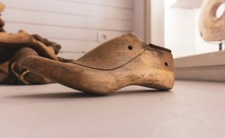 Wooden shoe mold used  for making shoes, lying on the white floor