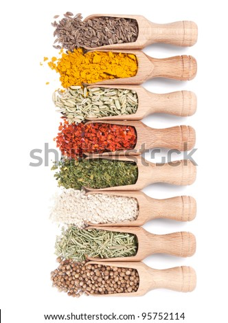 Wooden shovels with different spices scattered from them on white background