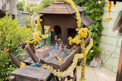 Wooden shrine with many dolls and flowers in Thailand.