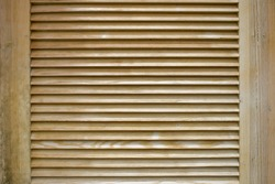 Wooden shutters. Window with wooden doors to protect from sunlight. Background with textured narrow boards. Modern shutters made of natural wood. Horizontal planks texture