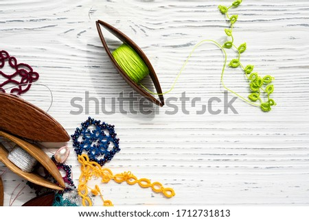 Wooden shuttles for weaving lace tatting with multi-colored threads, lace patterns with woven beads and pearls on a white wooden background. Close up. Copy space. Photo stock ©