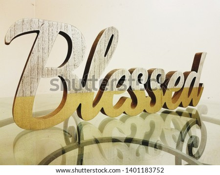 """Wooden sign """"blessed"""" on glass table"""