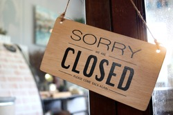 Wooden sign board that says 'closed' on cafe or restaurant hang on door at entrance.