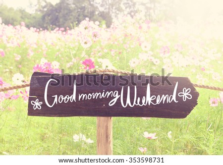 Wooden sign on blurred flowers background with vintage filter