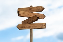 Wooden sign post isolated on blue sky with white clouds. Direction concept. Mock up, template