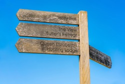 Wooden sign post with directions against blue sky in Epping Forest in Essex, England