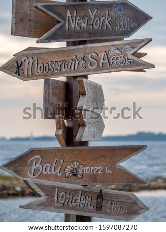 Wooden sign with arrows to destinations far away in other countries: New York, Mooserwirt S.A., Bali and London.