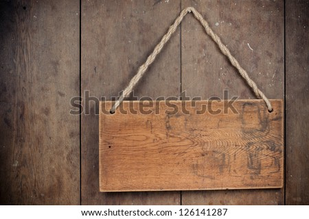 Wooden signboard with rope hanging on grunge planks background