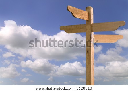 Wooden signpost against a blue cloudy sky, blank for your own text.