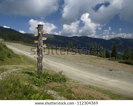 Wooden signpost by the mountain path - stock photo